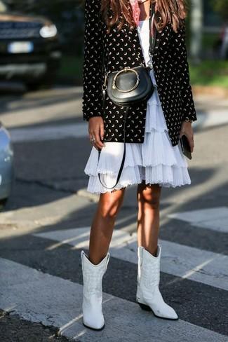 Come indossare: blazer stampato nero e bianco, vestito svasato con volant bianco, stivali da cowboy in pelle bianchi, borsa a tracolla in pelle nera
