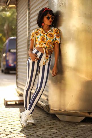 Come indossare: blusa abbottonata a fiori gialla, jeans aderenti a righe verticali bianchi e blu scuro, sneakers alte bianche, cerchietto rosso