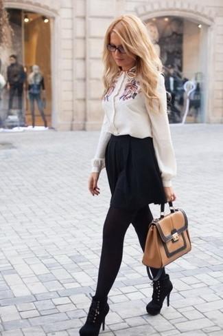 Come indossare: blusa abbottonata ricamata bianca, gonna a pieghe nera, stivaletti in pelle scamosciata neri, cartella in pelle marrone chiaro