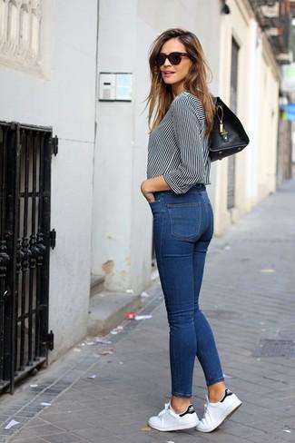 Come indossare: blusa abbottonata a righe verticali bianca e nera, jeans aderenti blu, sneakers basse di tela bianche, cartella in pelle nera