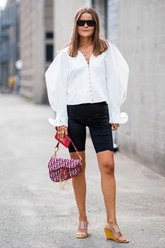 Come indossare: blusa abbottonata bianca, pantaloncini ciclisti neri, sandali con zeppa di gomma trasparenti, cartella di tela stampata viola melanzana