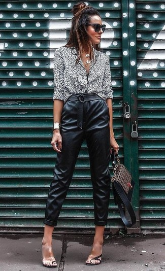 Come indossare e abbinare: blusa abbottonata leopardata bianca e nera, pantaloni stretti in fondo in pelle neri, sandali con tacco di gomma trasparenti, cartella in pelle stampata marrone