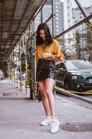Come indossare: camicetta manica corta a pois senape, minigonna in pelle nera, scarpe sportive bianche, cartella in pelle nera