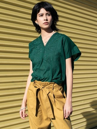 Come indossare e abbinare: camicetta manica corta verde scuro, pantaloni stretti in fondo marrone chiaro