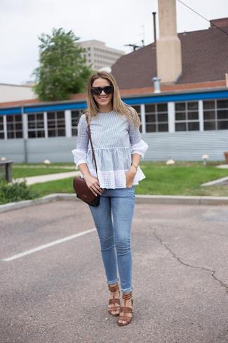 Come indossare e abbinare: camicetta manica lunga azzurra, jeans aderenti azzurri, sandali con tacco in pelle marroni, borsa a tracolla in pelle bordeaux