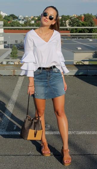 Come indossare: camicetta manica lunga con volant bianca, minigonna di jeans blu, sandali con zeppa in pelle marrone chiaro, borsa a secchiello in pelle marrone scuro