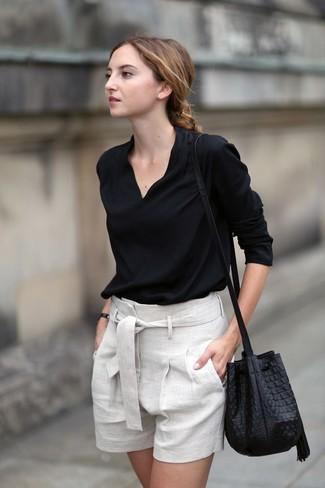 Come indossare: camicetta manica lunga nera, pantaloncini di lino beige, borsa a secchiello in pelle nera