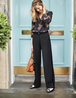 Come indossare: camicetta manica lunga a fiori nera, pantaloni larghi neri, mocassini con nappine in pelle scamosciata neri e bianchi, borsa shopping in pelle marrone chiaro