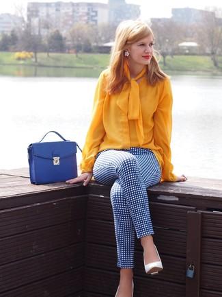 Come indossare: camicetta manica lunga gialla, pantaloni skinny a quadri bianchi e blu, décolleté in pelle bianchi, cartella in pelle blu
