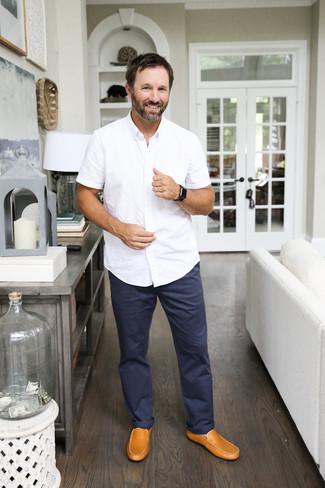 Trend da uomo: Combina una camicia a maniche corte bianca con chino blu scuro per un outfit comodo ma studiato con cura. Mocassini driving in pelle marrone chiaro sono una interessante scelta per completare il look.