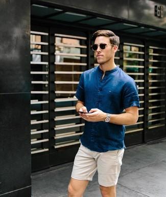 Come indossare e abbinare: camicia a maniche corte blu scuro, pantaloncini beige, occhiali da sole marrone scuro, orologio di tela grigio
