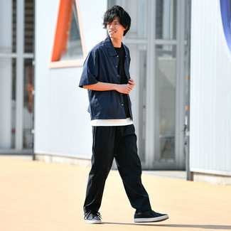 Trend da uomo 2021: Combina una camicia a maniche corte blu scuro con chino neri per un look trendy e alla mano. Sneakers basse in pelle nere sono una validissima scelta per completare il look.