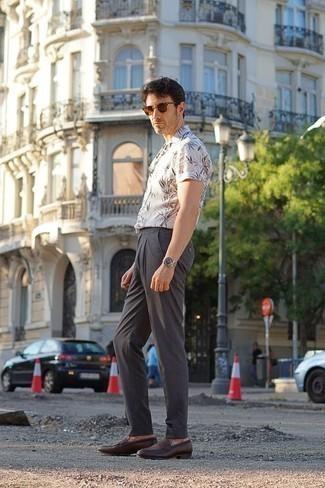 Trend da uomo 2020: Punta su una camicia a maniche corte stampata bianca e chino grigio scuro per un look trendy e alla mano. Scegli uno stile classico per le calzature e opta per un paio di mocassini eleganti in pelle marrone scuro.