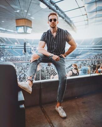 Come indossare e abbinare: camicia a maniche corte a righe verticali nera e bianca, jeans aderenti strappati blu, sneakers basse in pelle bianche, occhiali da sole neri