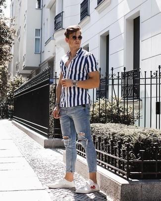 Trend da uomo: Abbina una camicia a maniche corte a righe verticali blu scuro e bianca con jeans aderenti strappati azzurri per una sensazione di semplicità e spensieratezza. Sfodera il gusto per le calzature di lusso e opta per un paio di sneakers basse stampate bianche.