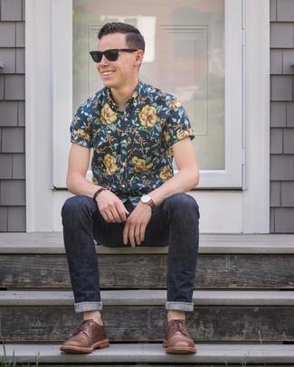 Moda uomo anni 20: Potresti indossare una camicia a maniche corte a fiori blu scuro e jeans blu scuro per un look trendy e alla mano. Sfodera il gusto per le calzature di lusso e indossa un paio di scarpe derby in pelle marroni.