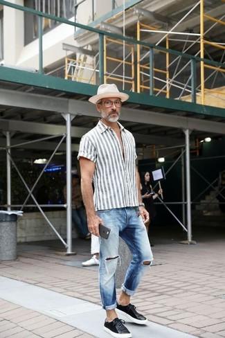 Come indossare e abbinare: camicia a maniche corte a righe verticali grigia, jeans strappati azzurri, sneakers basse in pelle nere, borsalino di paglia bianco