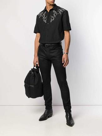 Come indossare e abbinare: camicia a maniche corte ricamata nera, jeans neri, stivali chelsea in pelle neri, zaino di tela nero