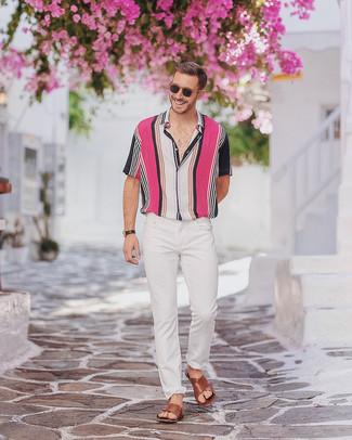 Come indossare: camicia a maniche corte a righe verticali multicolore, jeans aderenti bianchi, sandali in pelle marroni, orologio in pelle nero