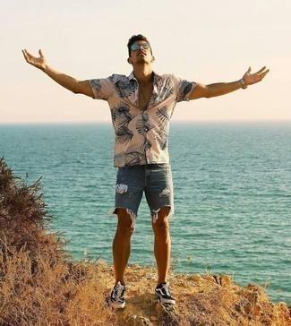 Trend da uomo 2020 in modo rilassato: Abbina una camicia a maniche corte stampata beige con pantaloncini strappati blu per una sensazione di semplicità e spensieratezza. Sneakers basse di tela stampate nere e bianche doneranno eleganza a un look altrimenti semplice.