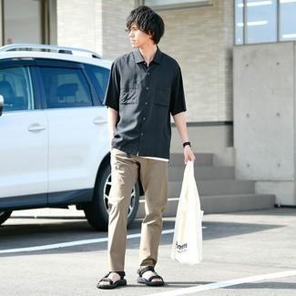 Trend da uomo 2021: Punta su una camicia a maniche corte nera e chino marrone chiaro per un look raffinato per il tempo libero. Non vuoi calcare troppo la mano con le scarpe? Scegli un paio di sandali di tela neri per la giornata.