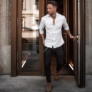 Come indossare e abbinare: camicia a maniche lunghe a righe verticali bianca, jeans aderenti neri, stivali casual in pelle marroni