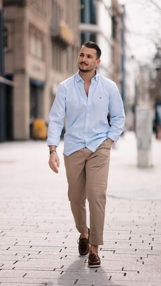 Trend da uomo: Per creare un adatto a un pranzo con gli amici nel weekend opta per una camicia a maniche lunghe azzurra e chino marrone chiaro. Perfeziona questo look con un paio di scarpe da barca in pelle marrone scuro.