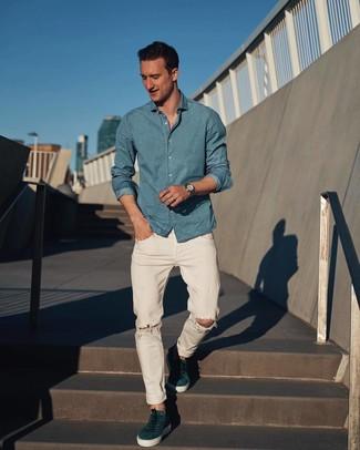 Come indossare e abbinare: camicia a maniche lunghe in chambray azzurra, jeans strappati bianchi, sneakers basse in pelle scamosciata foglia di tè, orologio argento