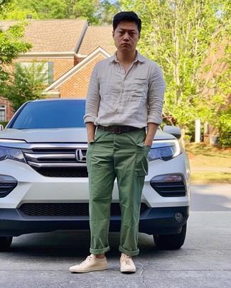 Come indossare e abbinare: camicia a maniche lunghe di lino beige, pantaloni cargo verdi, sneakers basse in pelle beige, cintura in pelle marrone scuro
