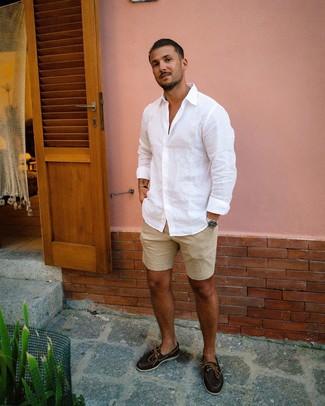 Come indossare e abbinare: camicia a maniche lunghe di lino bianca, pantaloncini marrone chiaro, scarpe da barca in pelle marrone scuro, orologio argento