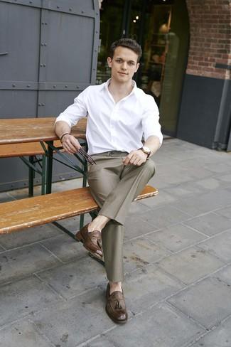 Come indossare e abbinare: camicia a maniche lunghe bianca, pantaloni eleganti marroni, mocassini con nappine in pelle marroni, orologio in pelle marrone scuro