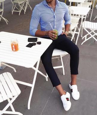 Come indossare e abbinare: camicia a maniche lunghe a righe verticali blu, chino blu scuro, sneakers basse in pelle stampate bianche, orologio dorato