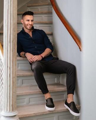 Come indossare: camicia a maniche lunghe blu scuro, chino neri, sneakers senza lacci in pelle nere, orologio in pelle nero