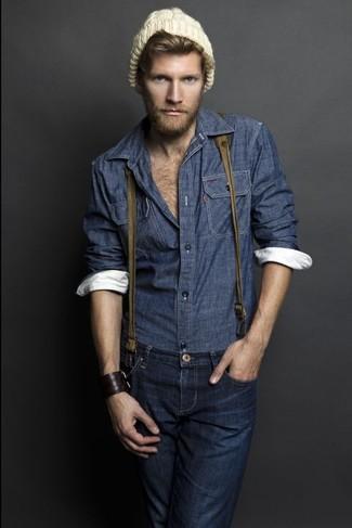 Come indossare e abbinare: camicia a maniche lunghe in chambray blu scuro, jeans blu scuro, berretto marrone chiaro, bretelle verde oliva