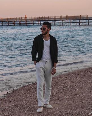 Trend da uomo 2021: Scegli una camicia a maniche lunghe nera e chino grigi per un look spensierato e alla moda. Rifinisci questo look con un paio di espadrillas di tela a righe orizzontali grigie.