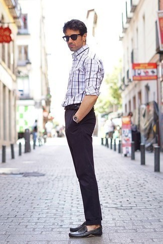 Trend da uomo 2020: Una giornata impegnativa richiede un outfit semplice ma elegante, come una camicia a maniche lunghe scozzese bianca e blu scuro e chino blu scuro. Un paio di mocassini driving in pelle neri si abbina alla perfezione a una grande varietà di outfit.