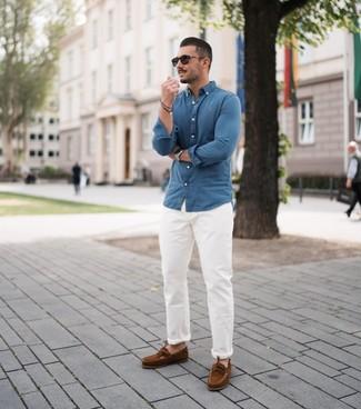 Come indossare e abbinare: camicia a maniche lunghe in chambray blu, chino bianchi, scarpe da barca in pelle scamosciata marroni, occhiali da sole neri