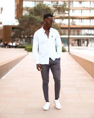 Moda uomo anni 20: Coniuga una camicia a maniche lunghe bianca con chino grigio scuro per un look raffinato per il tempo libero. Non vuoi calcare troppo la mano con le scarpe? Indossa un paio di sneakers basse di tela bianche per la giornata.