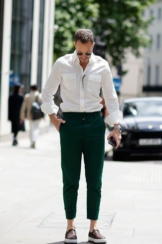 Come indossare e abbinare chino verde scuro: Metti una camicia a maniche lunghe bianca e chino verde scuro per un outfit comodo ma studiato con cura. Sneakers senza lacci in pelle marrone scuro sono una splendida scelta per completare il look.