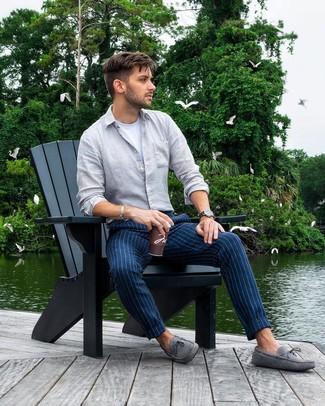 Come indossare: camicia a maniche lunghe di lino grigia, t-shirt girocollo bianca, chino a righe verticali blu scuro, mocassini driving in pelle scamosciata grigi