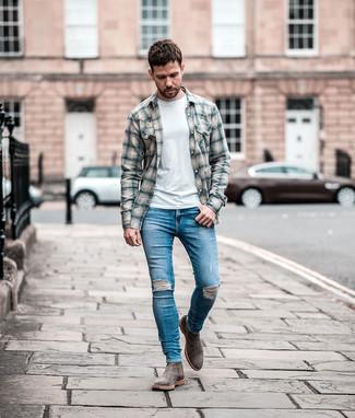 Come indossare e abbinare: camicia a maniche lunghe di flanella scozzese grigia, t-shirt girocollo bianca, jeans aderenti strappati blu, stivali chelsea in pelle scamosciata grigi