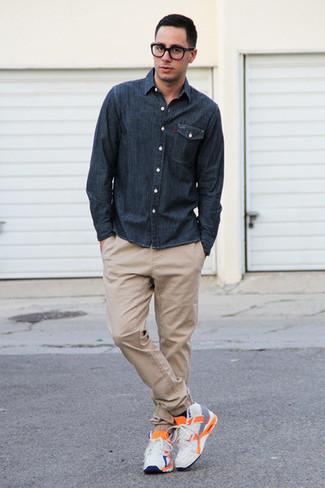Come indossare e abbinare: camicia a maniche lunghe in chambray blu scuro, chino marrone chiaro, scarpe sportive bianche