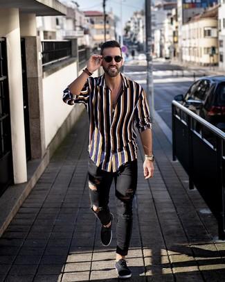Come indossare e abbinare: camicia a maniche lunghe a righe verticali blu scuro, jeans aderenti strappati neri, sneakers basse di tela nere, occhiali da sole neri