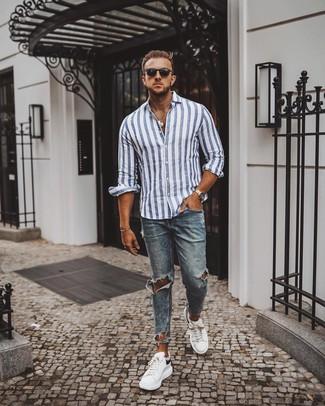 Come indossare e abbinare: camicia a maniche lunghe a righe verticali bianca e blu, jeans aderenti strappati blu, sneakers basse in pelle bianche e nere, occhiali da sole neri