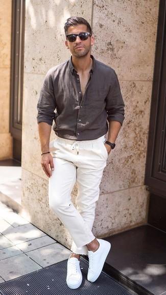 Trend da uomo quando fa molto caldo: Mostra il tuo stile in una camicia a maniche lunghe di lino marrone scuro con jeans bianchi per un pranzo domenicale con gli amici. Questo outfit si abbina perfettamente a un paio di sneakers basse bianche.