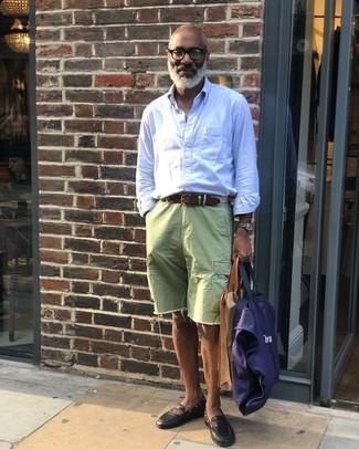 Come indossare e abbinare: camicia a maniche lunghe a righe verticali azzurra, pantaloncini di jeans verdi, mocassini eleganti in pelle neri, borsa shopping di tela blu scuro