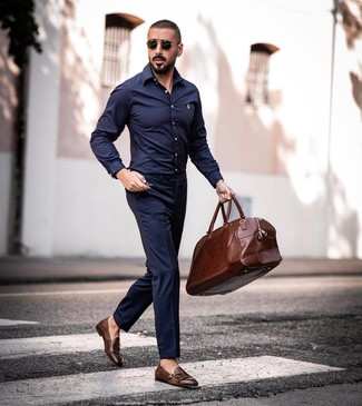 Come indossare e abbinare: camicia a maniche lunghe blu scuro, pantaloni eleganti blu scuro, scarpe double monk in pelle marroni, borsone in pelle marrone