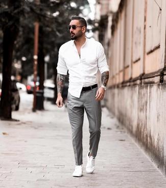 Come indossare e abbinare: camicia a maniche lunghe bianca, pantaloni eleganti grigi, sneakers basse in pelle bianche, cintura in pelle nera