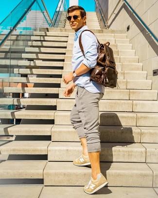 Come indossare e abbinare: camicia a maniche lunghe azzurra, pantaloni sportivi grigi, sneakers basse marrone chiaro, zaino in pelle marrone