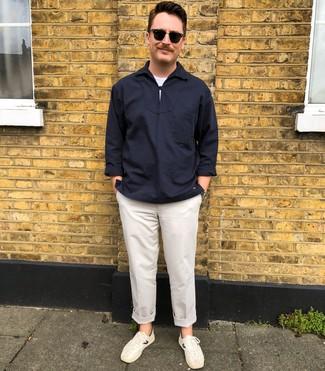 Come indossare e abbinare: camicia a maniche lunghe blu scuro, t-shirt girocollo bianca, chino bianchi, sneakers basse bianche
